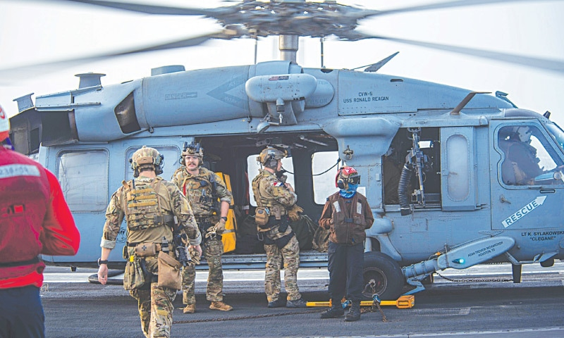 US Navy sailors board an MH-60S Seahawk helicopter on the flight deck of aircraft carrier USS Ronald Reagan to head to an oil tanker that was attacked off the coast of Oman in the Arabian Sea on Friday. — AP