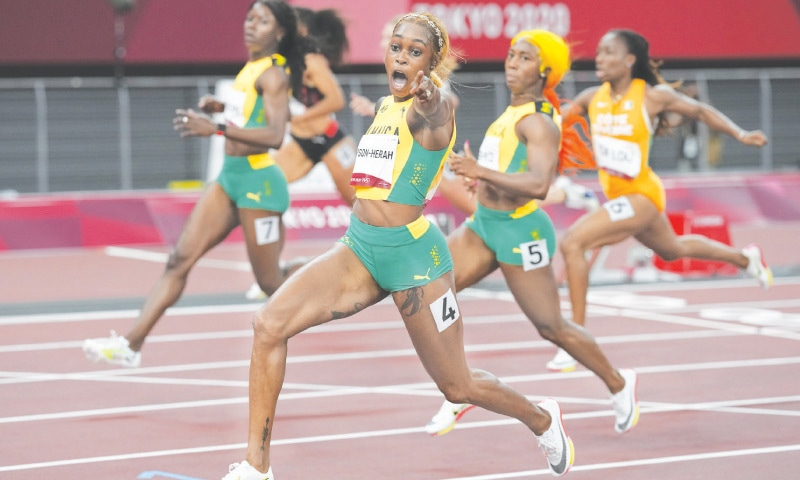TOKYO: Elaine Thompson-Herah of Jamaica celebrates as she wins the women's 100-metre final at the Olympic Stadium on Saturday.—AP