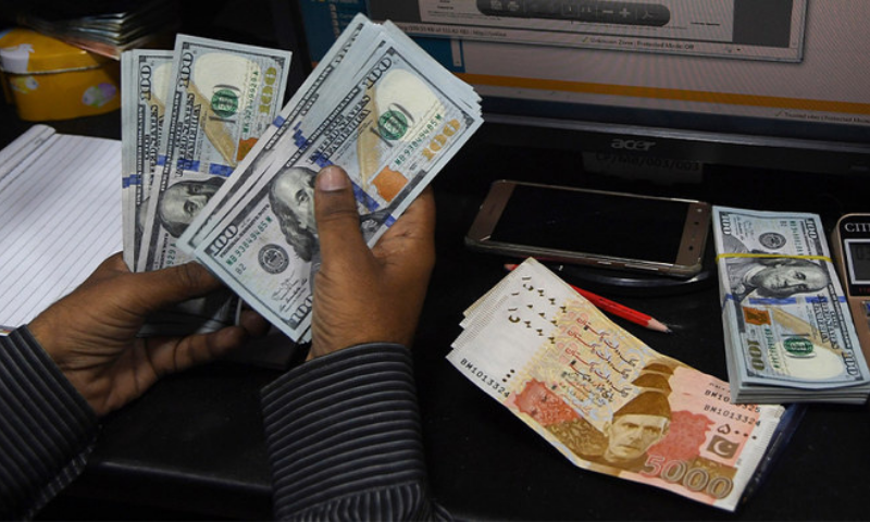 A dealer counts US dollars at a currency exchange shop in Karachi. — AFP/File