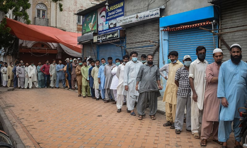 People queue up and wait to get themselves inoculated with a Covid-19 vaccine at a vaccination centre in Karachi. — AFP