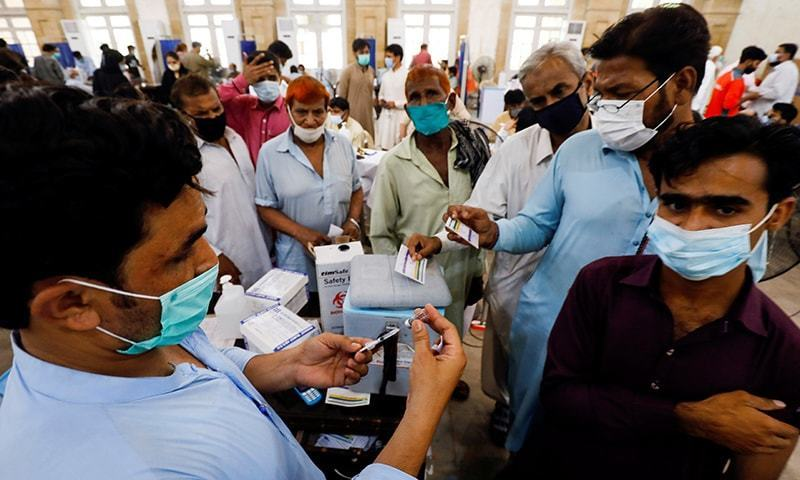 Residents with their registration cards gather at a counter to receive a dose of coronavirus vaccine at a vaccination centre in Karachi on June 9. — Reuters/File