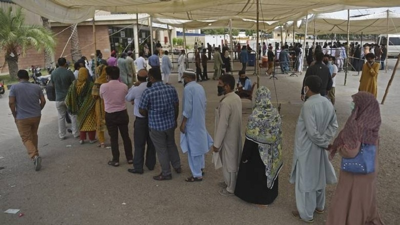 People wait for their turn to receive a dose of the Covid-19 vaccine at a camp organised in Karachi. — AFP/File