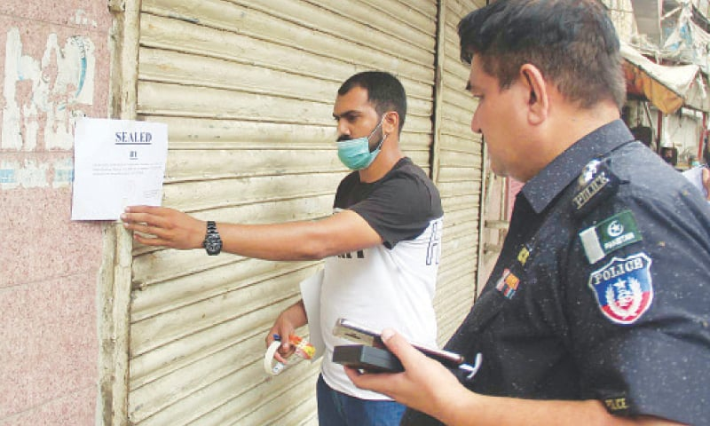 City government teams seal shops in different areas of Karachi on Sunday for violating SOPs aimed at curbing the spread of Covid-19.—Online