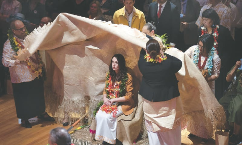 New Zealand's Prime Minister Jacinda Ardern is ritually covered in a mat during a ceremony at which she apologised for excesses against the Pacific community.—AP