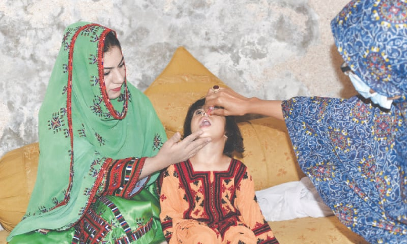 RAIMA Mengal helps administer anti-polio drops to a girl during a campaign.—Dawn