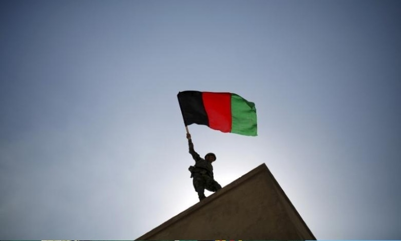An Afghan National Army officer holds an Afghanistan flag during a training exercise at the Kabul Military Training Centre in Afghanistan October 7, 2015. — Reuters