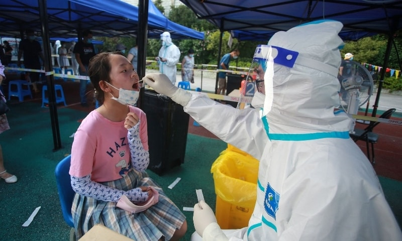 This photo taken on August 1, 2021 shows a resident receiving a nucleic acid test for the Covid-19 coronavirus in Yangzhou in China's eastern Jiangsu province. — AFP