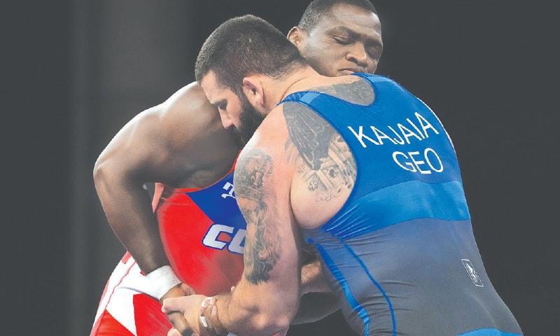 CUBA'S Mijain Lopez Nunez (L) and Lakobi Kajaia of Georgia compete during the men's 130kg Greco-Roman wrestling final.—AP