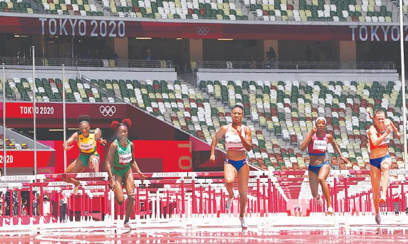 JASMINE Camacho-Quinn of Puerto Rico (third R) leads to win the women's 100m hurdles final at the Olympic Stadium on Monday.—Reuters