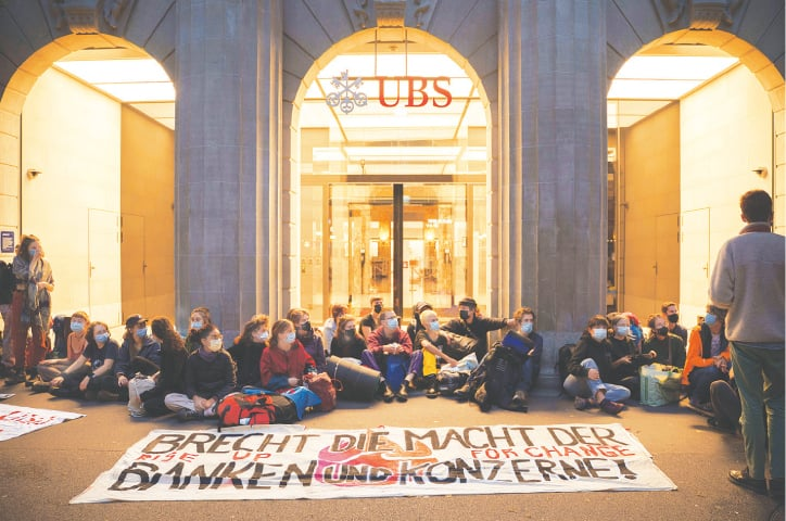 ZURICH (Germany): Climate activists block an entrance of the Union Bank of Scotland on Monday to protest big banks' financing of fossil fuel projects that damage the environment.—Reuters