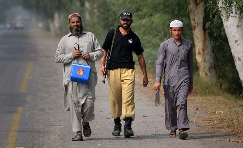 In this file photo, a policemen accompanies polio workers on an immunisation campaign. — Reuters/File