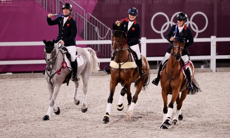 Gold medallists Oliver Townend of Britain, Laura Collett of Britain and Tom McEwen of Britain celebrate after winning the Equestrian Eventing Jumping competition on Monday. — AP