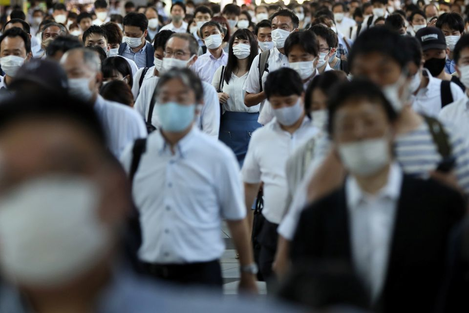 Commuters wearing face masks arrive at Shinagawa Station at the start of the working day in Tokyo, Japan, August 2. — Reuters