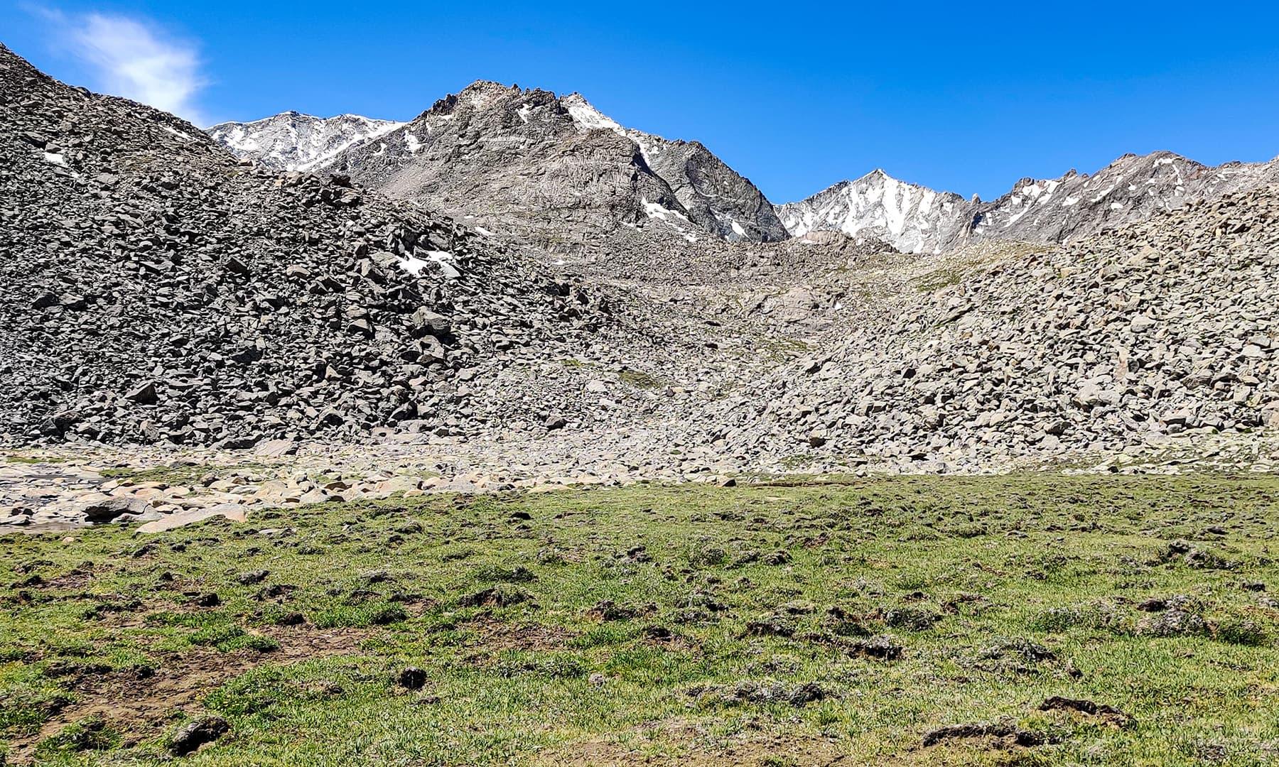 مخملی گھاس اور پتھریلی بلندیاں جھیل تک پہنچنے کا واحد راستہ ہیں