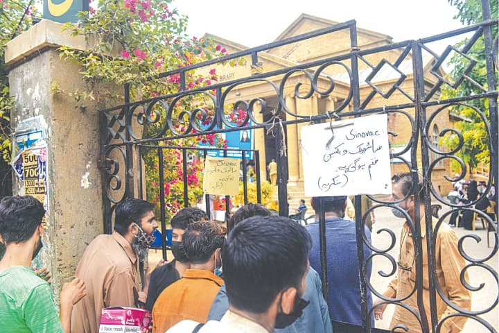 A sign outside the Khaliqdina Hall on Tuesday tells people that the centre has run out of SinoVac vaccines.—Fahim Siddiqi/White Star