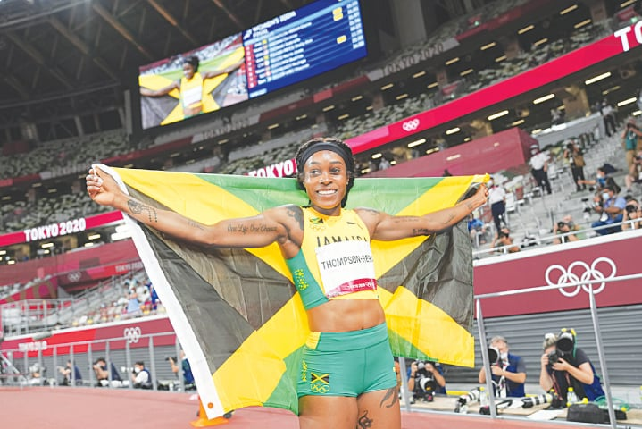 TOKYO: Jamaica's Elaine Thompson-Herah poses for photographers after winning the gold medal in the women's 200 metres final at the Olympic games on Tuesday. Her blistering sprint, which followed her brilliant 100m victory, made her the first woman to win both the Olympic events twice in a row. She had won both titles at the 2016 Olympics as well.—AP