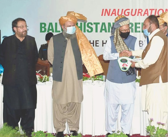 QUETTA: President Dr Arif Alvi handing over the key of a tractor to a farmer during the ceremony on Tuesday.—PPI