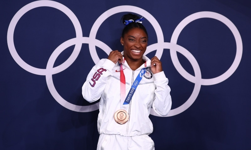 Bronze medallist Simone Biles of the United States poses in front of the Olympic rings on August 3. — Reuters