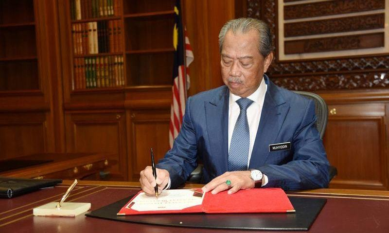 Malaysia's Prime Minister Muhyiddin Yassin signs a document on his first day at the prime minister's office in Putrajaya, Malaysia on March 2, 2020. — Reuters/File