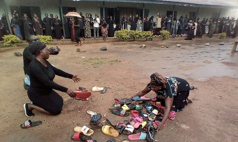 Parents of students abducted at Bethel Baptist High School pray for their safe return around discarded shoes left behind by the children, in Kaduna, Nigeria, July 9. — Reuters/File