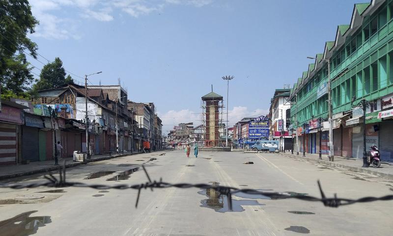 Kashmiri women walk at the deserted Lal Chowk square in Srinagar, occupied Kashmir. — AP