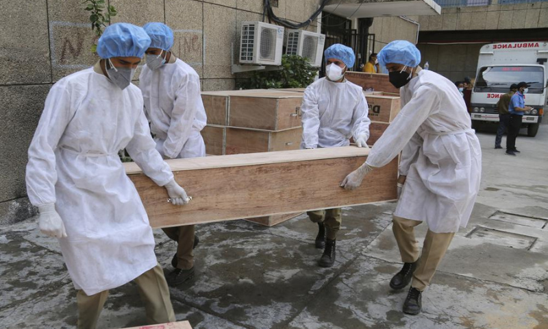 Jammu and Kashmir State Disaster Response Force soldiers carry empty coffins for transporting bodies of people who died of Covid-19 outside government medical hospital in Jammu, occupied Kashmir on May 19. — AP