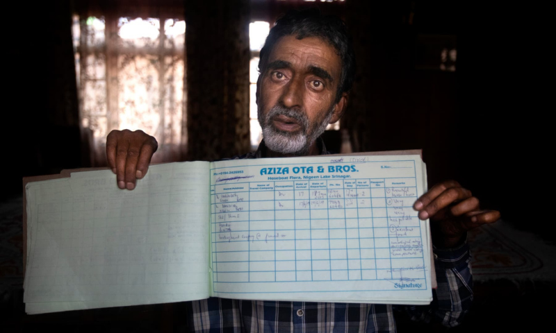 A Kashmiri houseboat owner Ghulam Qadir shows his guest entry book which was last filled in July 2019, in Srinagar. — AP