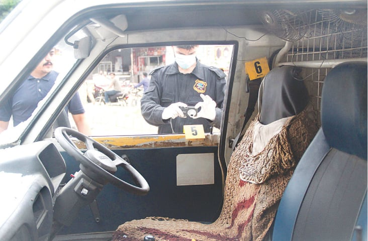 Police investigators examine the vehicle that came under attack on Wednesday.—Online