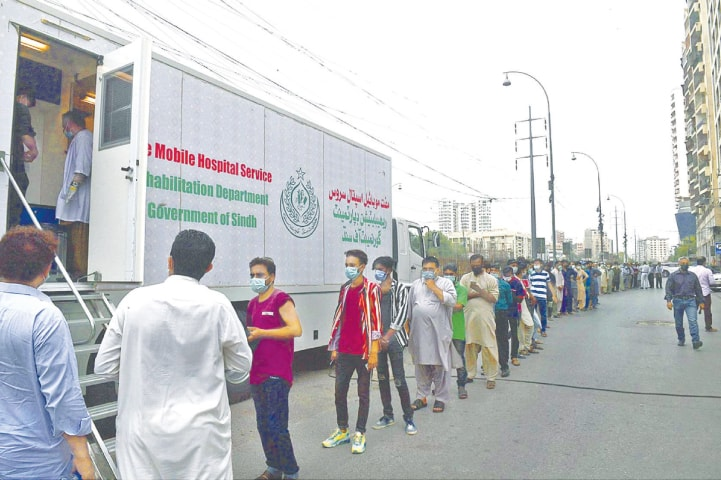 KARACHI: People in a long queue wait for their turn outside a mobile vaccination centre in the Clifton area on Wednesday to get jabs against Covid-19.—APP