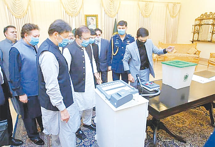 ISLAMABAD: Prime Minister Imran Khan being briefed on functions of the electronic voting machine.—White Star