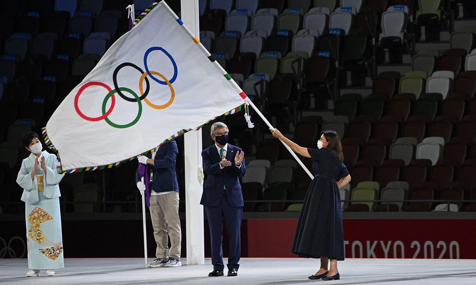 انٹرنیشنل اولممپک کمیٹی کے صدر تھامس بیچ نے اولمپک پرچم فرانس کے دارالحکومت پیرس کی میئر کے حوالے کیا جہاں اولمپک گیمز 2024 منعقد ہوں گے—فوٹو: اے ایف پی