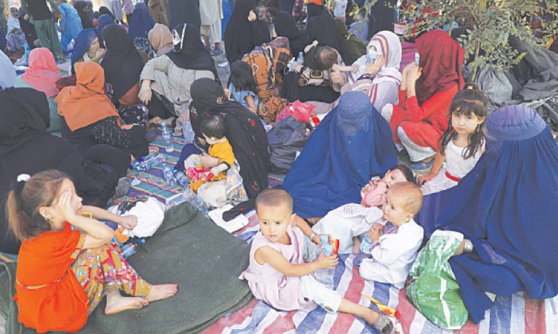 KABUL: Internally displaced Afghans from northern provinces, who fled their homes due to fighting between the Taliban and Afghan security forces, take refuge in a park on Monday.—AP