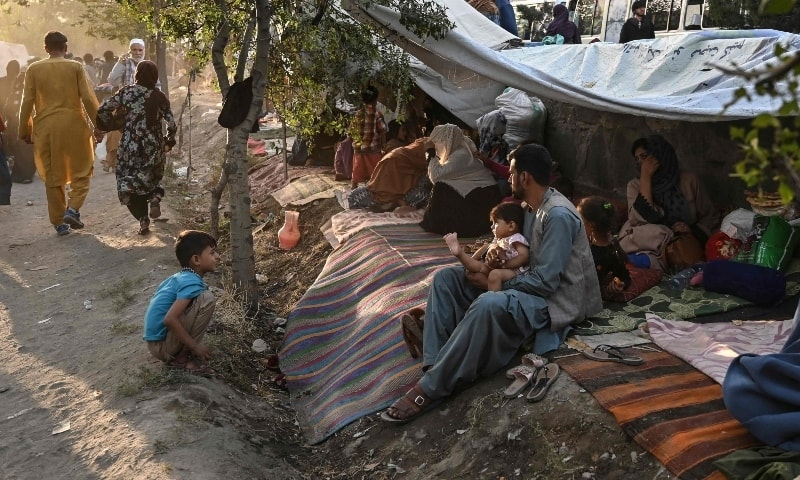 Internally displaced Afghan families, who fled from Kunduz, Takhar and Baghlan province due to battles between Taliban and Afghan security forces, sit in front of their temporary tents at Sara-e-Shamali in Kabul on August 11. — AFP