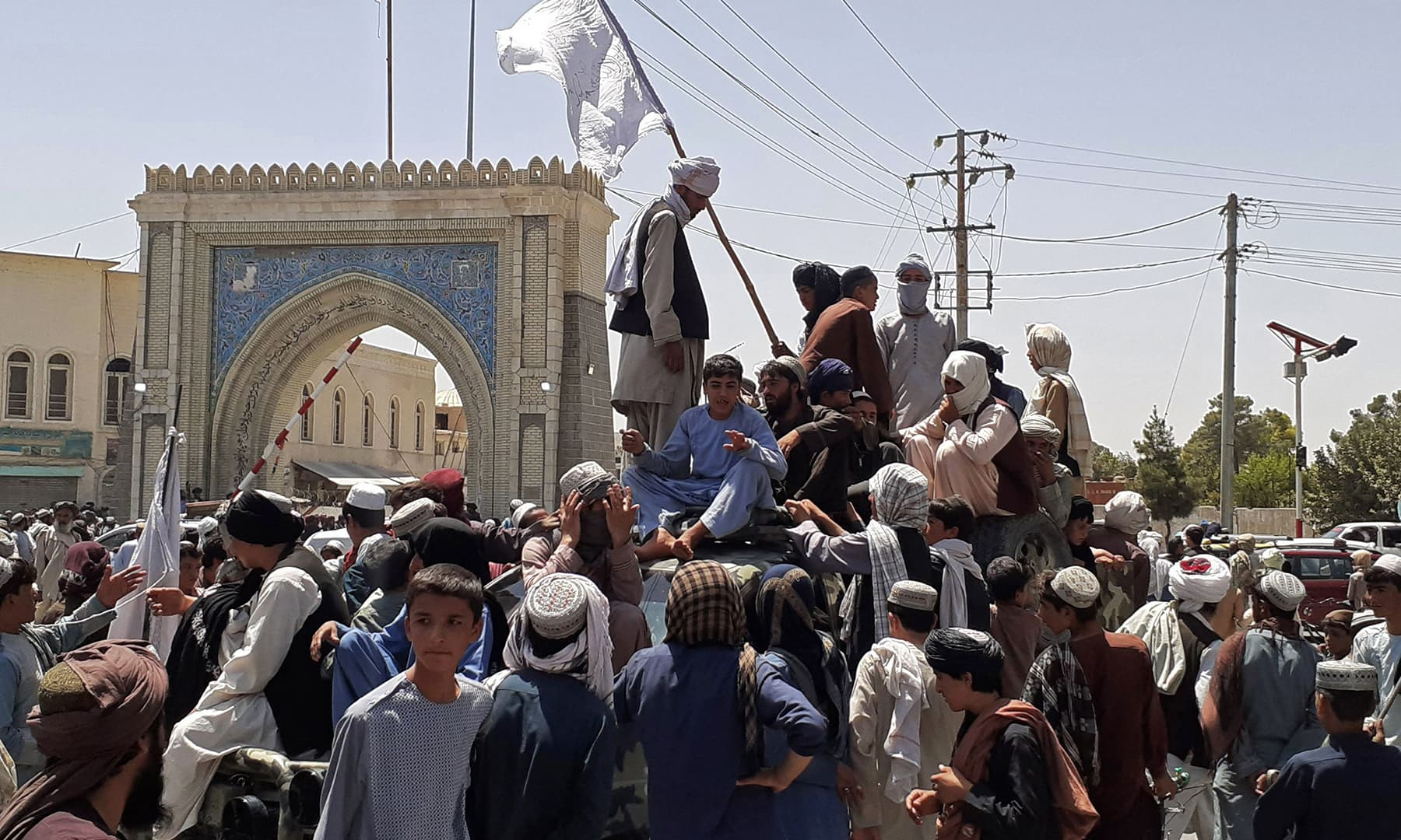 Taliban fighters stand on a vehicle along the roadside in Kandahar on August 13. — AFP