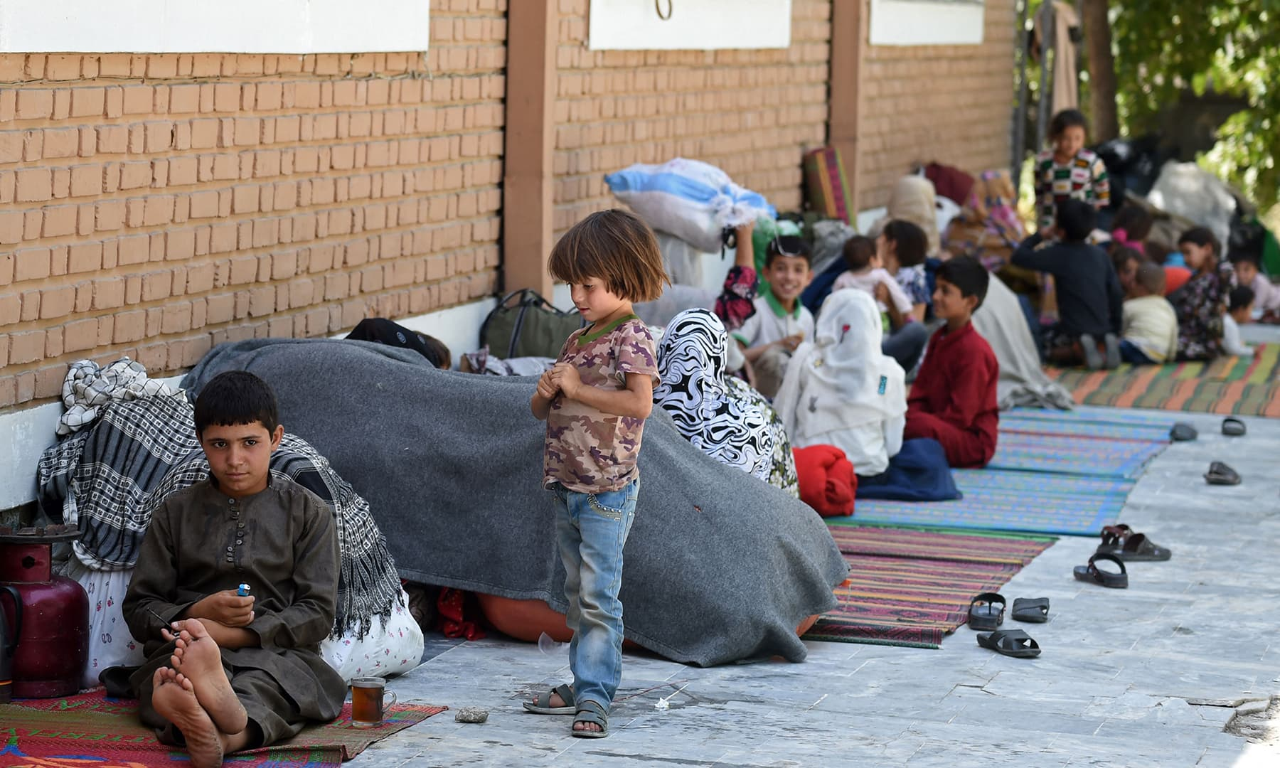 Internally displaced Afghan families, who fled from the northern province due to fighting between the Taliban and Afghan security forces, sit in the courtyard of the Wazir Akbar Khan mosque in Kabul on August 13. — AFP