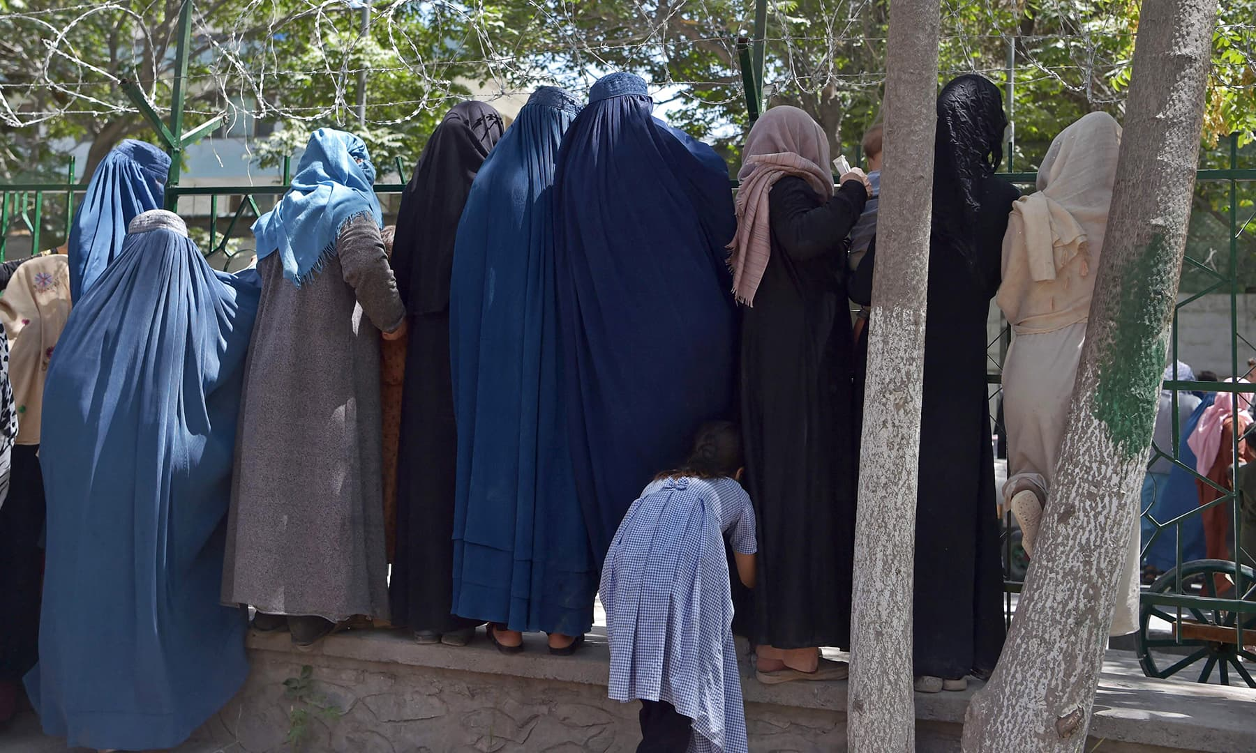 Internally displaced Afghan women, who fled from the northern province due to battles between the Taliban and Afghan security forces, gather to receive free food being distributed at Shahr-e-Naw Park in Kabul on August 13. — AFP
