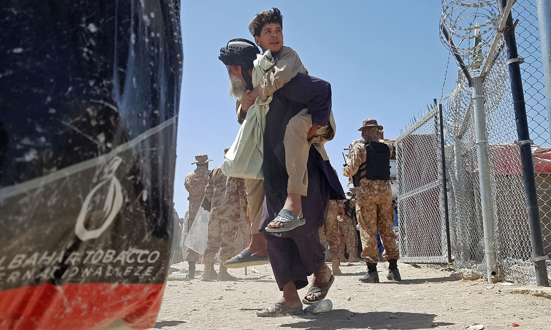 A stranded Afghan national carries his son at the Pakistan-Afghanistan border-crossing point in Chaman on August 13. — AFP