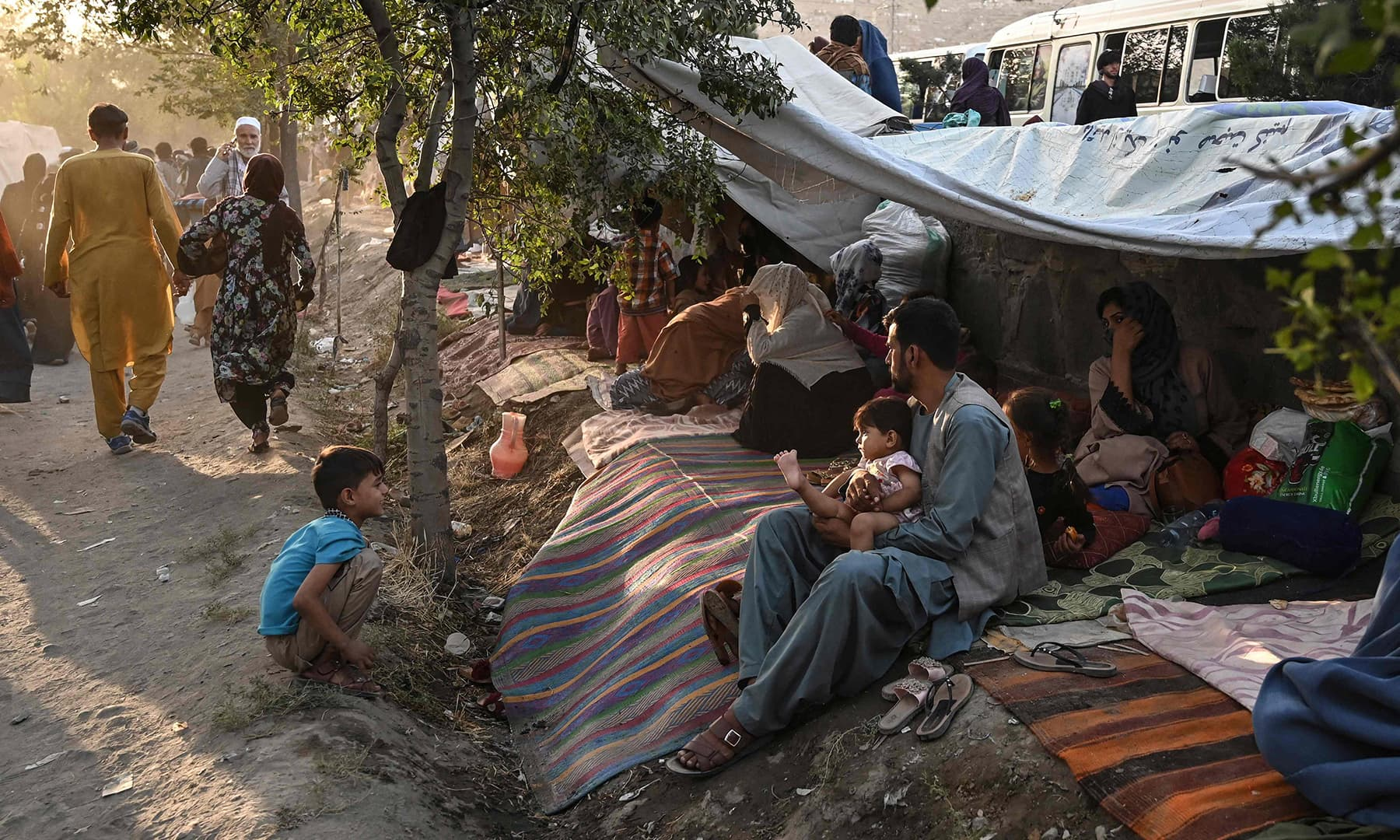 Internally displaced Afghan families, who fled from Kunduz, Takhar and Baghlan provinces due to battles between Taliban and Afghan security forces, sit in front of their temporary tents at Sara-e-Shamali in Kabul on August 11. — AFP