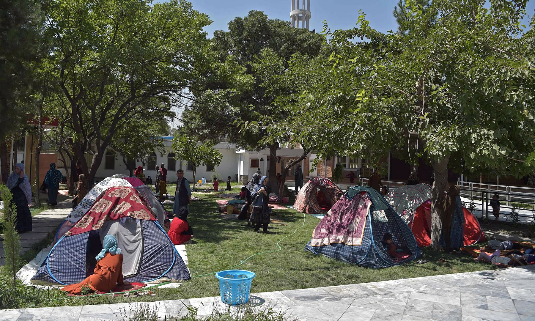 Internally displaced Afghan families, who fled from the northern province due to battles between the Taliban and Afghan security forces, sit in temporary tents in the courtyard of the Wazir Akbar Khan mosque in Kabul on August 13. — AFP