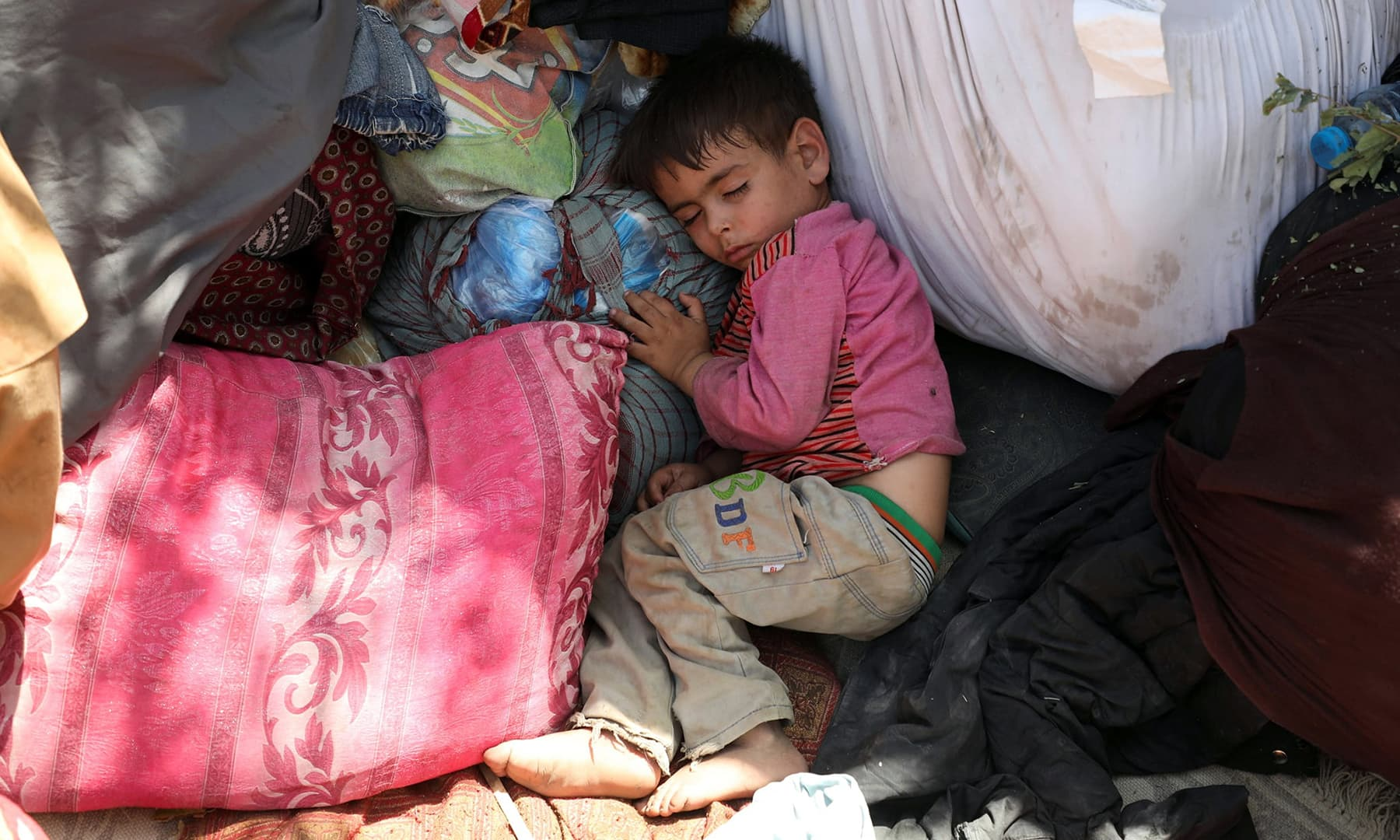 An internally displaced child from northern provinces, who fled from his home due to the fighting between Taliban and Afghan security forces, sleeps in a public park that they use as shelter in Kabul, Afghanistan, August 10. — Reuters