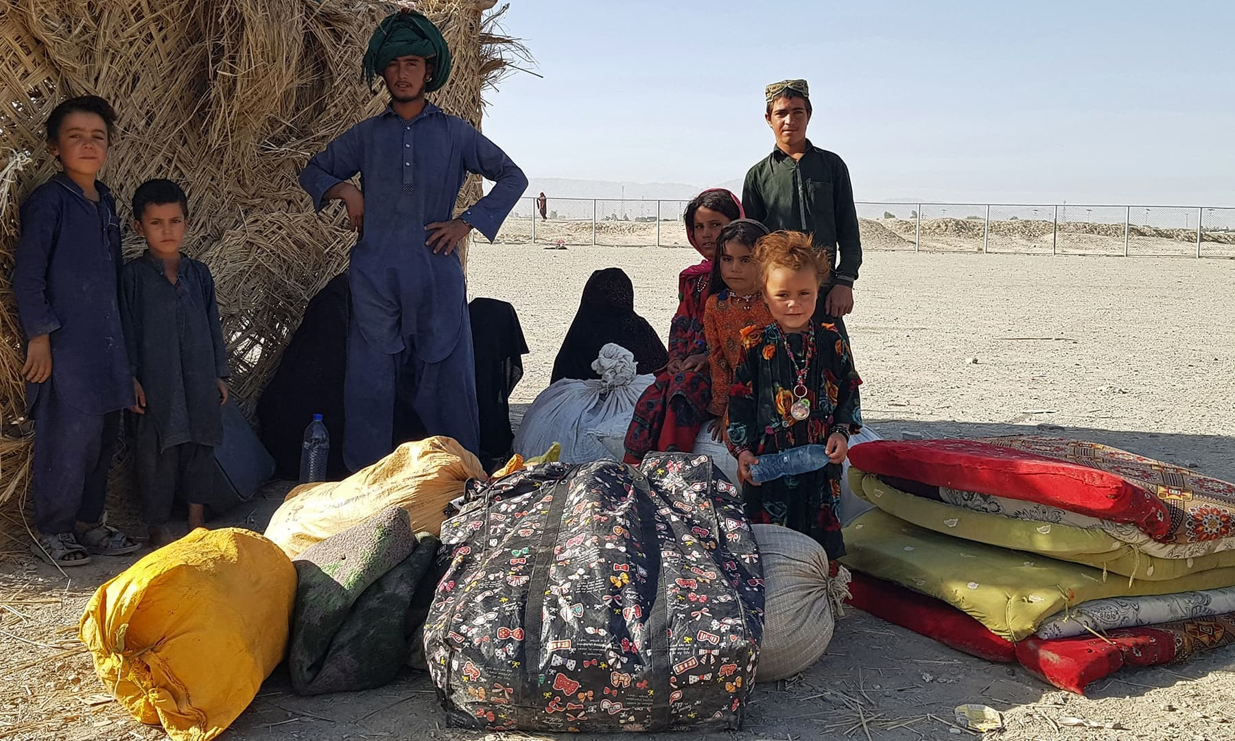 TOPSHOT - A stranded Afghan family waits for the reopening of the Pakistan-Afghanistan border crossing point in Chaman on August 13, 2021, after the Taliban took control of the Afghan border town in a rapid offensive across the country. (Photo by - / AFP) — AFP or licensors