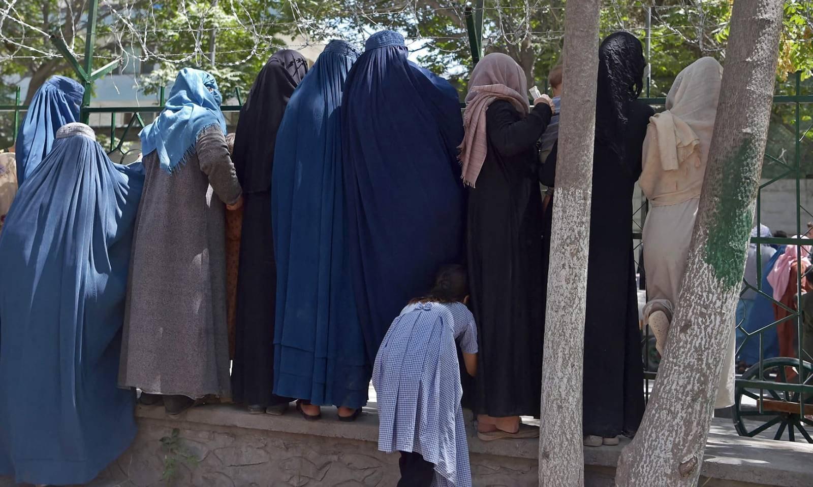 بے گھر ہونے والی افغان خواتین کابل کے شہرِ نو پارک میں مفت تقسیم ہونے والے کھانے کے لیے جمع ہو رہی ہیں — فوٹو: اے ایف پی