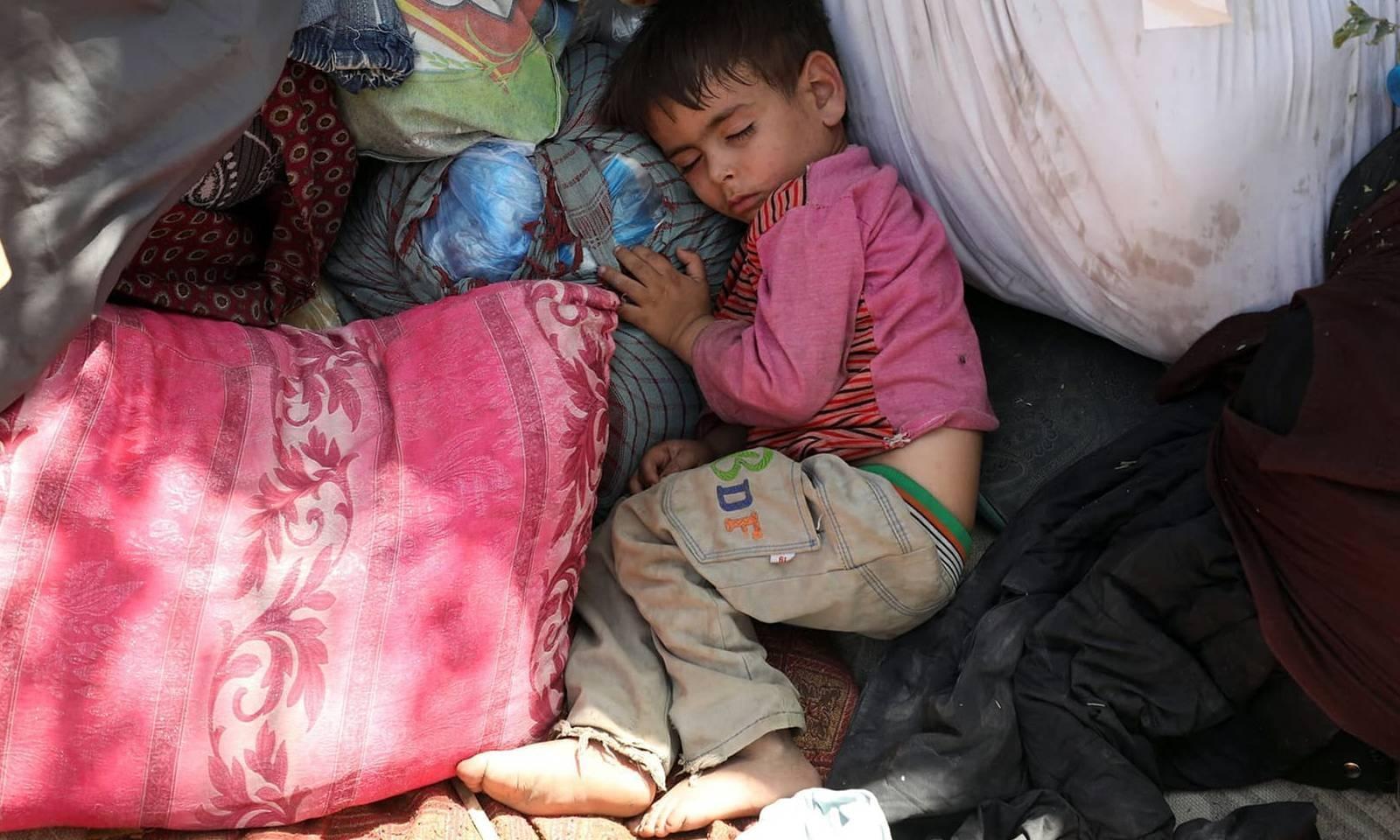 افغانستان کے شمالی صوبوں میں جھڑپوں کے دوران بے گھر ہونے والا بچہ ایک پارک میں سورہا ہے —فوٹو: اے ایف پی