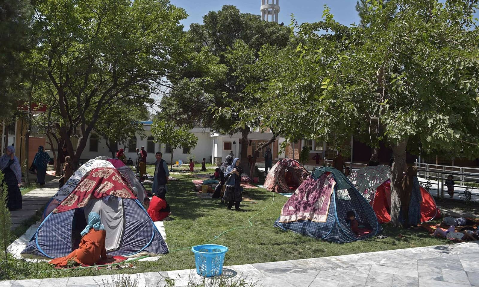 بے گھر ہونے والے افغان خاندان کابل میں مسجد کے صحن میں عارضی خیموں میں بیٹھے ہیں — فوٹو: اے ایف پی