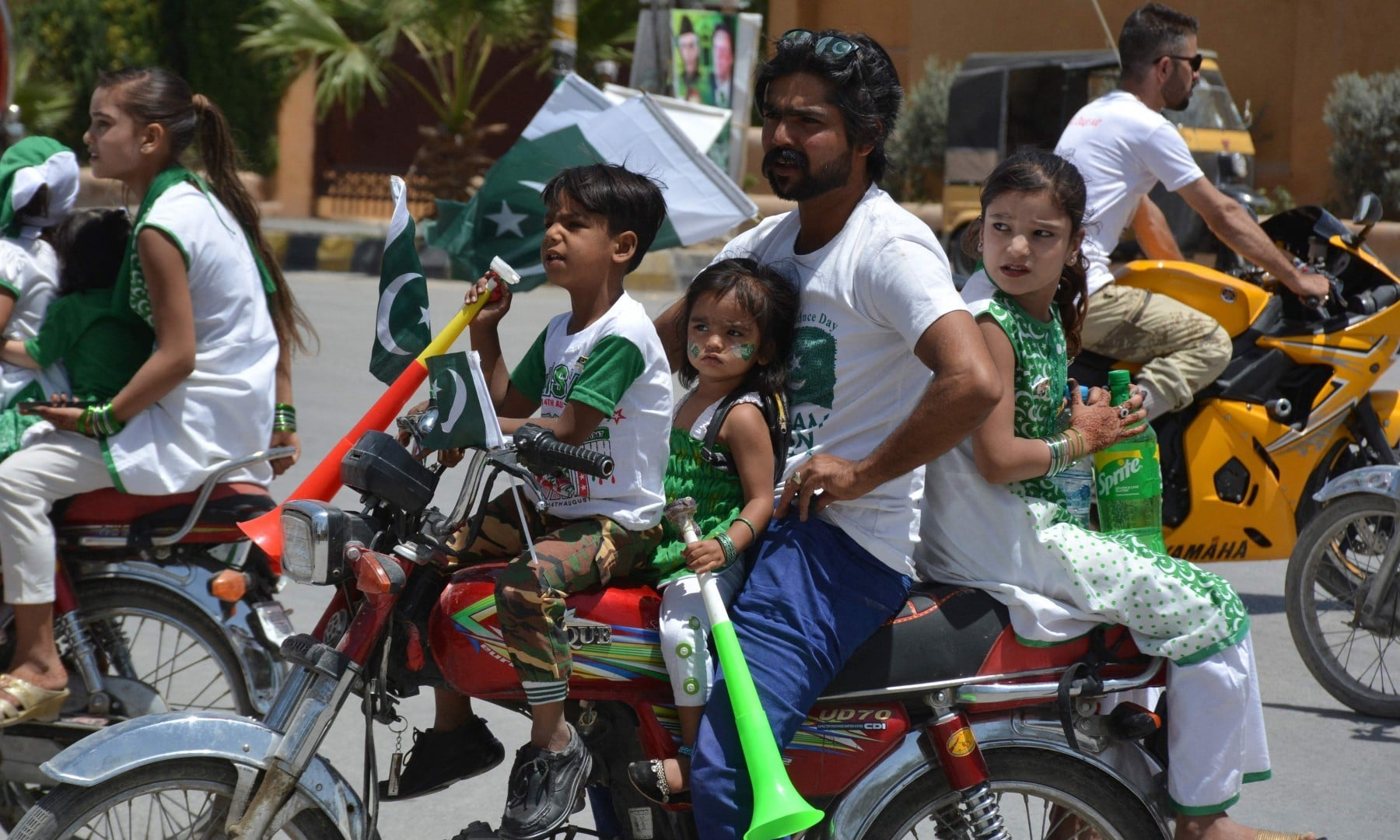A man along with children ride on a motorbike dressed in the colours of Pakistan's national flag during Independence Day celebrations in Quetta on August 14. — AFP