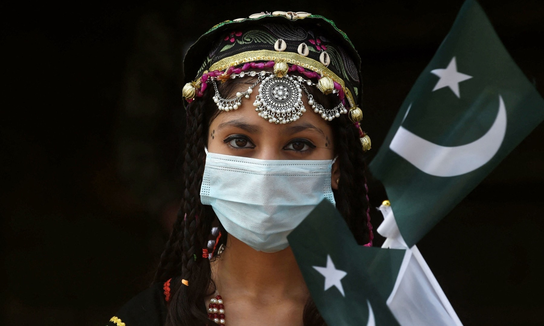 A girl poses for a picture with flags of Pakistan at the tomb of national poet Allama Mohammad Iqbal during Independence Day celebrations in Lahore on August 14. — AFP