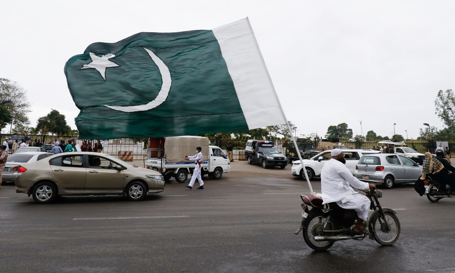 A man with a national flag on his bike rides during the celebrations of Independence Day in Karachi on August 14. — Reuters