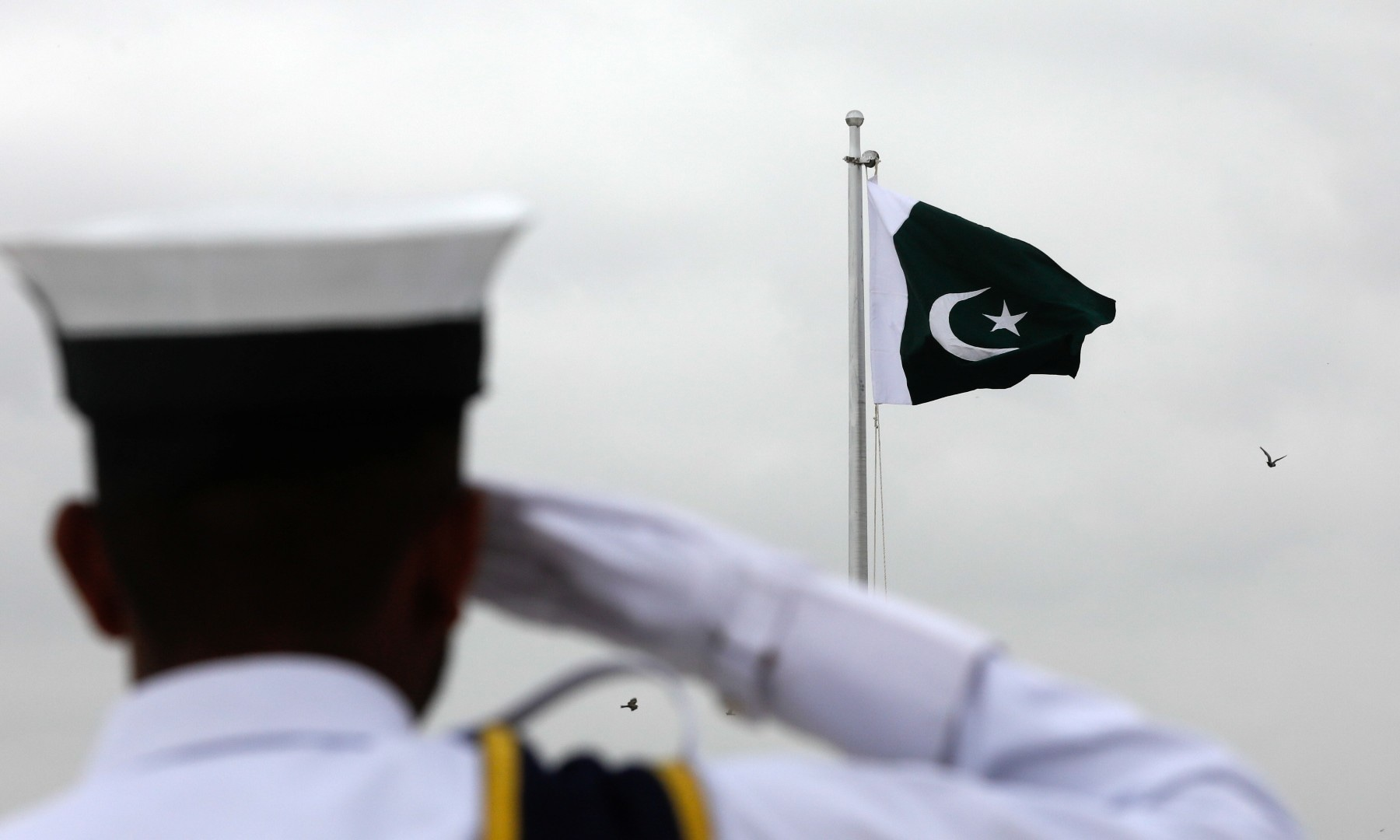 A cadet of the Pakistan Navy salutes the national flag during a flag hoisting ceremony to celebrate Independence Day at Quaid-i-Azam's mausoleum in Karachi on August 14. — Reuters