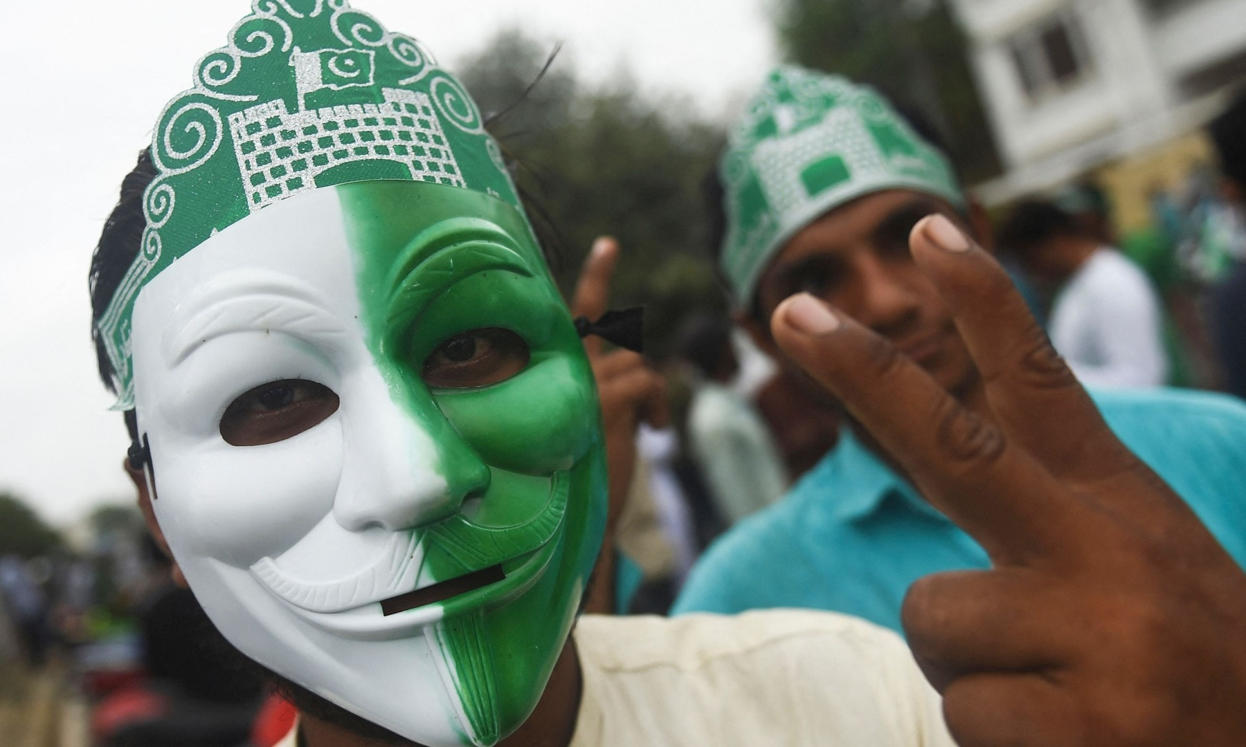 A man gestures while wearing a mask with the colours of the flag of Pakistan outside Quaid-i-Azam's mausoleum during Independence Day celebrations in Karachi on August 14. — AFP