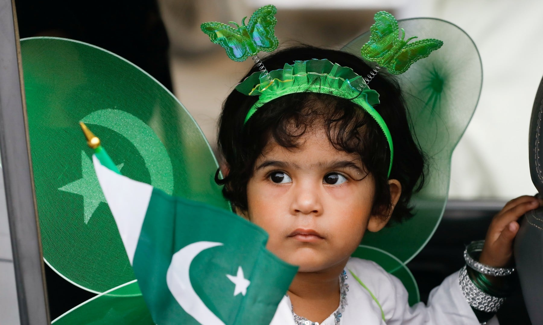 A girl waves a flag from a window of a car during Independence Day celebrations of in Karachi on August 14. — Reuters